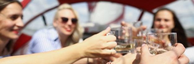 요트에 있는 쾌활한 젊은 여성들은 안경을 쓰고 웃는 여자 친구는 보트에서 즐거운 시간을 보낸다