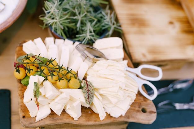 Молодой сыр с веточкой помидоров черри на тарелке с кухонными ножницами