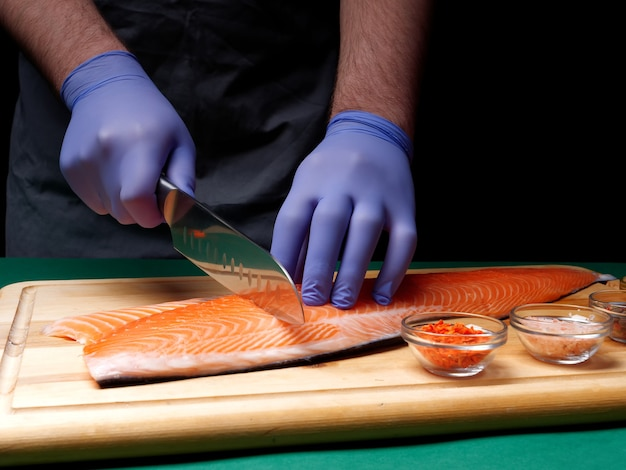 A young chef cuts a fresh raw salmon fillet and spices lie nearby on a wooden cutting board. healthy food concept