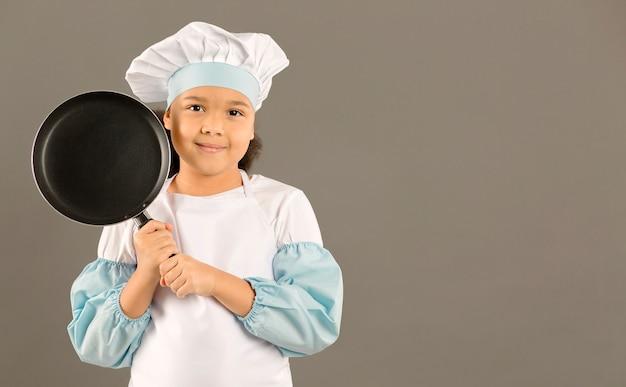 Молодой шеф-повар держит кастрюлю