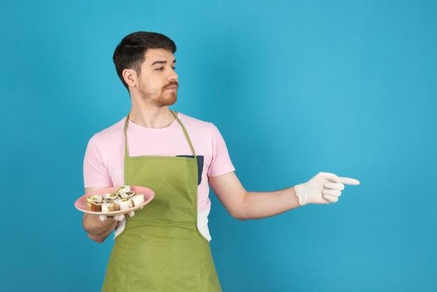 Un giovane chef che tiene in mano panini appena sfornati e punta il dito lontano.