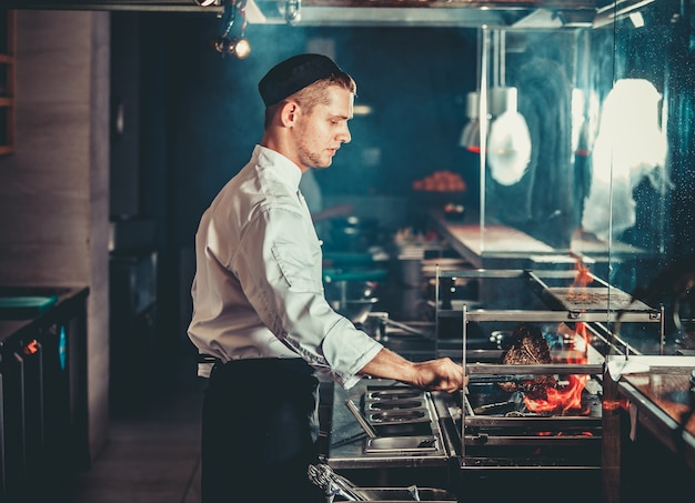 白い制服の肉を料理の若いシェフ