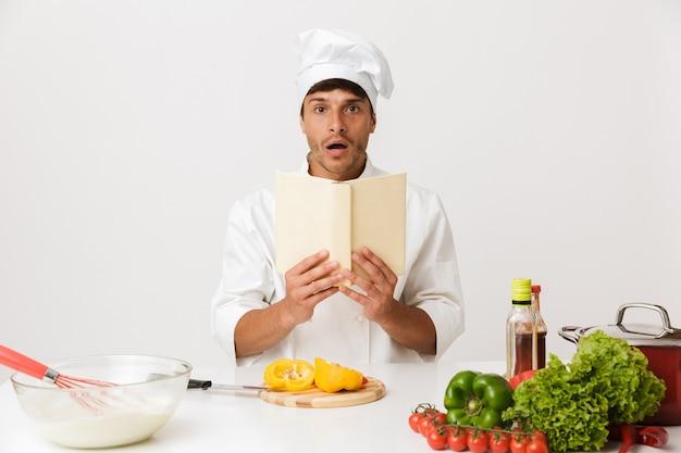本を読んで白い壁料理に孤立した若いシェフの男。