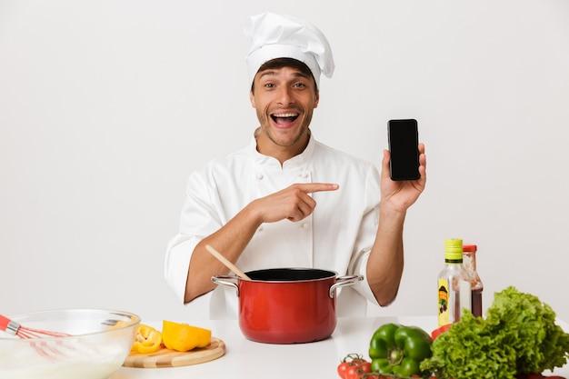 ディスプレイを指して携帯電話を使用して白い壁の料理に孤立した若いシェフの男。