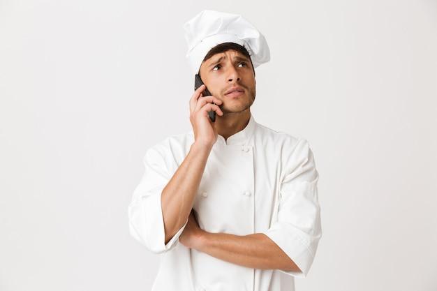Молодой человек шеф-повара изолированный на белой стене смотря в сторону говоря мобильным телефоном.
