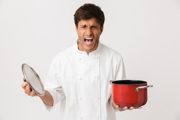 Молодой человек шеф-повара стоя изолированный на белой стене держа посуду.