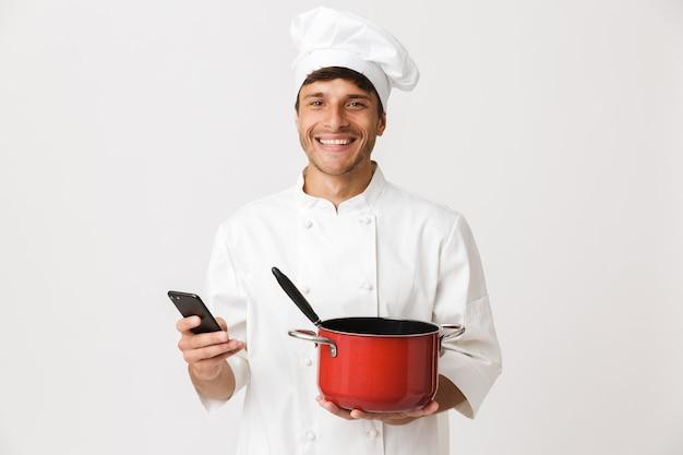 食器を保持している白い壁に孤立して立っている若いシェフの男。