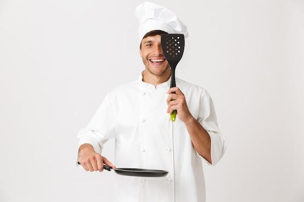 フライパン料理を保持している白い壁に孤立して立っている若いシェフの男。