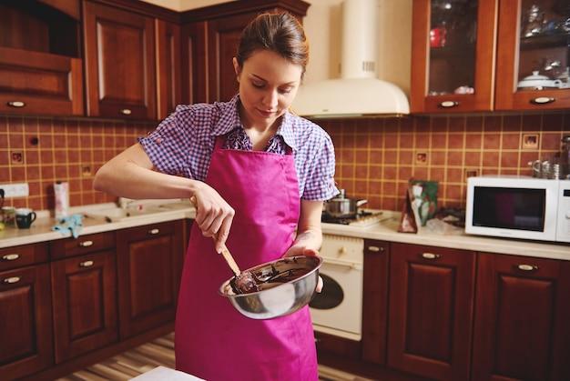 그녀의 집 부엌에서 녹은 초콜릿 덩어리를 혼합하는 젊은 요리사 과자. 세계 초콜릿의 날 기념 수제 사탕 제조