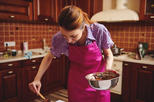 그녀의 집 부엌에서 녹은 초콜릿 덩어리로 수제 초콜릿을 준비하는 젊은 요리사 과자. 세계 초콜릿의 날 기념 수제 사탕 제조