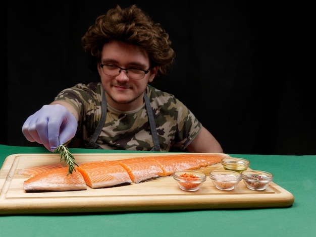 A young chef puts rosemary on a fresh raw salmon fillet which lies next to spices on a wooden cutting board nearby. healthy food concept