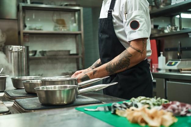 Руки молодого шеф-повара с татуировками готовят домашнюю итальянскую пасту на кухне ресторана