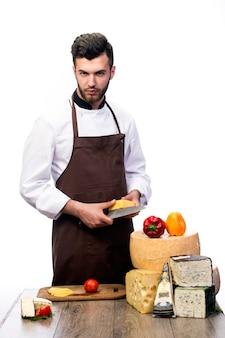 白い壁、チーズの広告に分離されたチーズを持つ若いシェフ