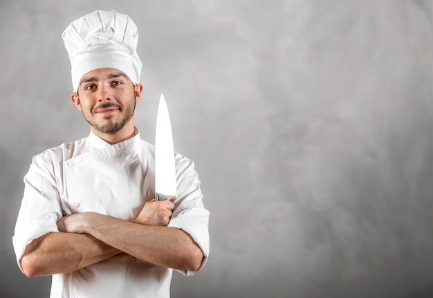 Young chef with knife posing with gray wall copyspace