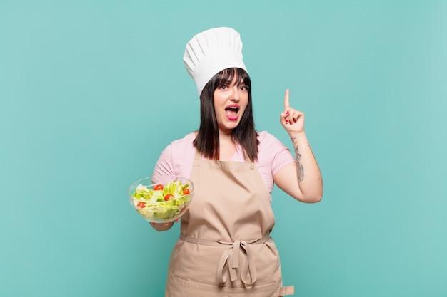 Молодая женщина-повар почувствовала себя счастливым и взволнованным гением, реализовав идею, весело подняв палец, эврика!