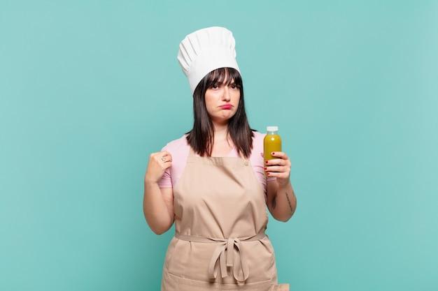 Молодая женщина-повар выглядит высокомерной, успешной, позитивной и гордой, указывая на себя