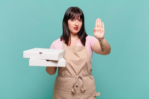 Молодая женщина-повар выглядит серьезной, строгой, недовольной и сердитой, показывая открытую ладонь, делая стоп-жест