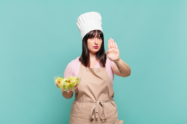 Young chef woman looking serious, stern, displeased and angry showing open palm making stop gesture