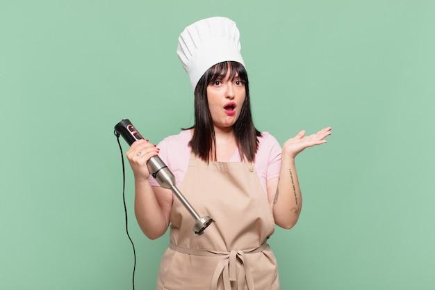 Молодая женщина-повар выглядит удивленной и шокированной, с отвисшей челюстью, держащей предмет с открытой рукой сбоку