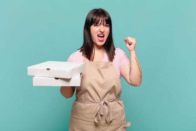 Молодая женщина-повар агрессивно кричит с сердитым выражением лица или со сжатыми кулаками празднует успех