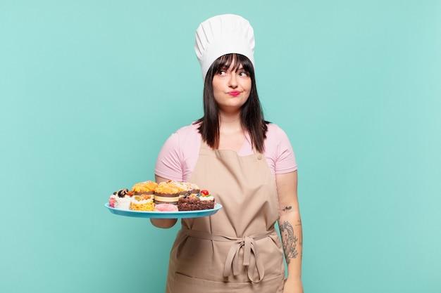 Молодая женщина-повар пожимает плечами, чувствуя смущение и неуверенность, сомневаясь, скрестив руки и озадаченный взгляд