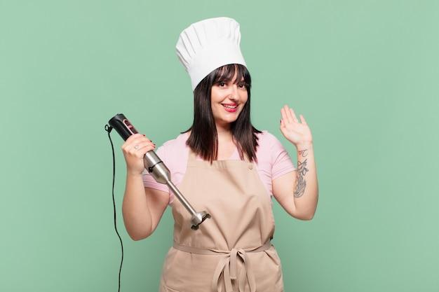 Молодая женщина-повар счастливо и весело улыбается, машет рукой, приветствует и приветствует вас или прощается