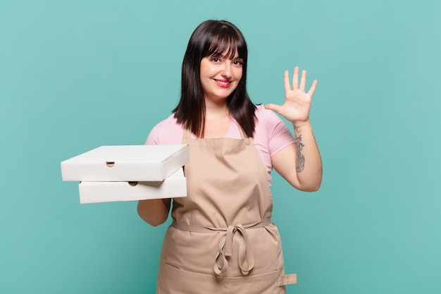 Young chef woman smiling and looking friendly, showing number five or fifth with hand forward, counting down