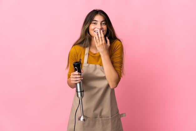 ピンクの幸せで笑顔の手で口を覆って分離されたハンドブレンダーを使用して若いシェフの女性