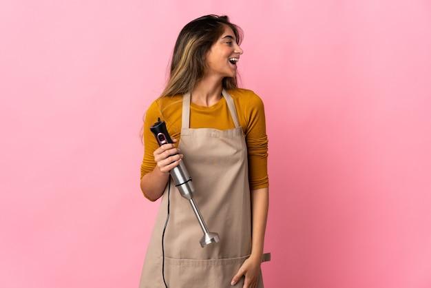 측면 위치에서 웃고 분홍색 벽에 고립 된 핸드 블렌더를 사용하는 젊은 요리사 여자