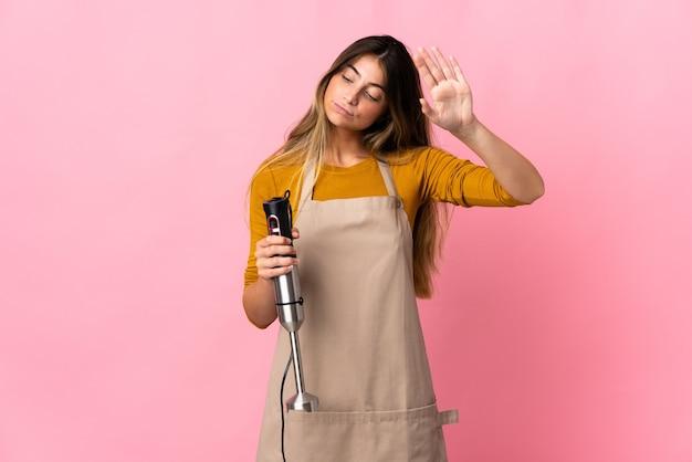 고립 된 핸드 블렌더를 사용 하여 젊은 요리사 여자