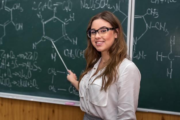 칠판에 있는 젊은 화학 교사는 포인터로 새로운 주제를 설명하고 보여줍니다. 학교로 돌아가다