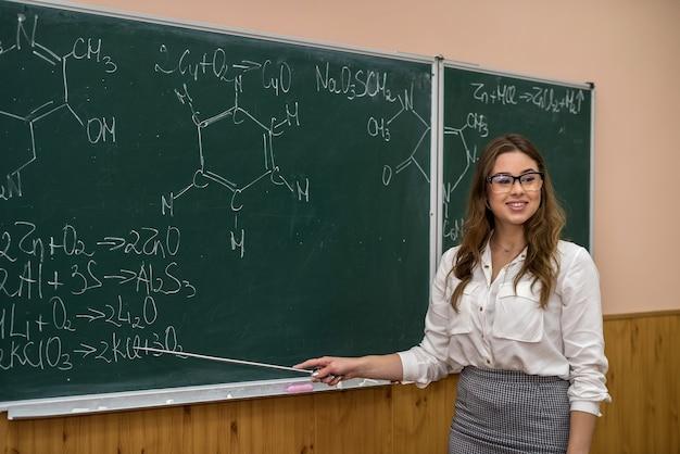 黒板の若い化学の先生は、新しいトピックをポインターで説明し、示します。学校に戻る