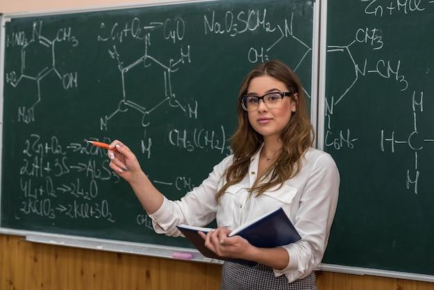 黒板の若い化学の先生が新しいトピックを説明し、ポインターで示します