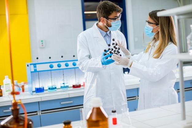 Молодые химики в защитных очках держат молекулярную модель в лаборатории