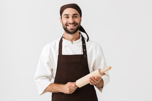 Young chief man in cook uniform smiling and holding kitchen wooden rolling pin isolated over white wall