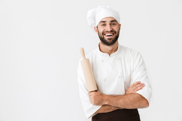 Young chief man in cook uniform smiling while holding kitchen wooden rolling pin isolated over white wall