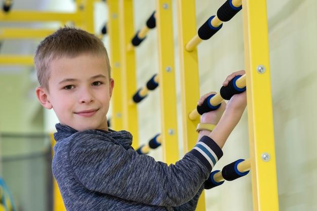 学校のスポーツジムの部屋の中の壁のはしごバーで運動する若い子少年。