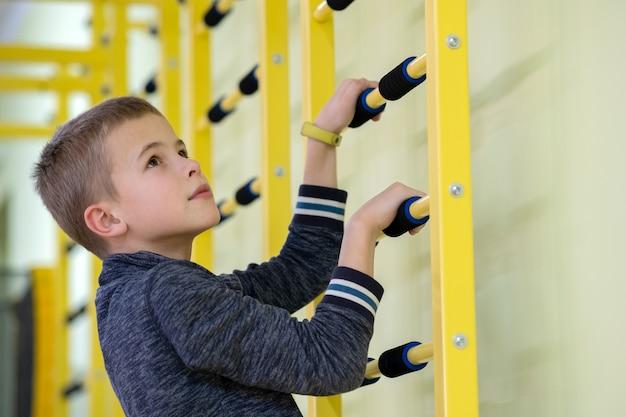 学校のスポーツジムの部屋の中の壁のはしごバーで運動する幼児少年。