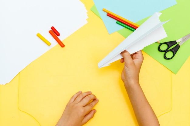 幼い子供の男の子の手は、黄色のテーブルのステップからステップへの白い紙の飛行飛行機を行います