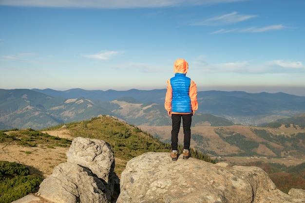 Путешественник мальчика маленького ребенка стоя в горах, наслаждаясь видом удивительного горного пейзажа.