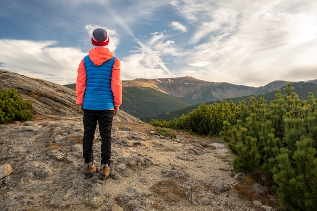 Young child boy hiker standing in mountains enjoying view of amazing mountain landscape