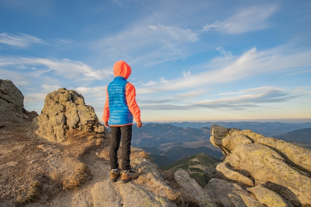 Young child boy hiker standing in mountains enjoying view of amazing mountain landscape.