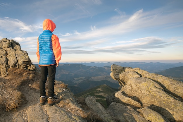Young child boy hiker standing in mountains enjoying view.