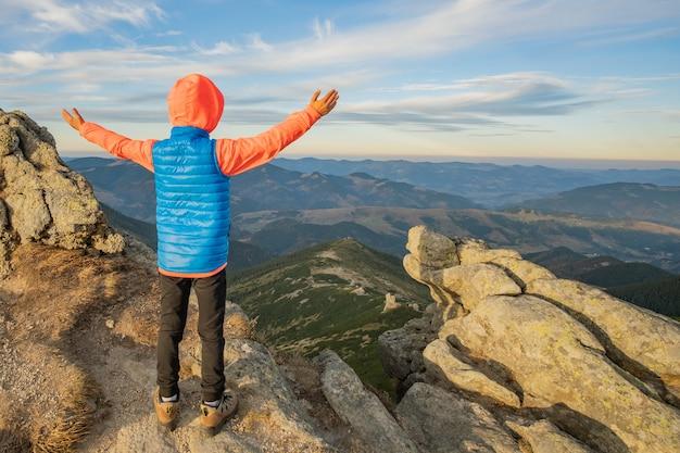 일몰에 놀라운 산 풍경을 즐기는 산에서 제기 손으로 서 어린 아이 소년 등산객.