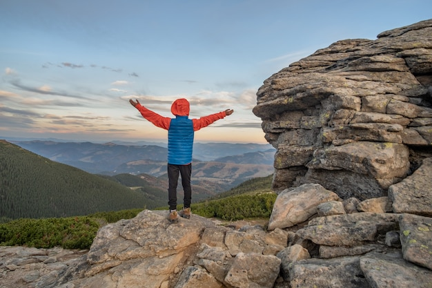 Young child boy hiker standing with raised hands in mountains enjoying view of amazing mountain landscape at sunset.