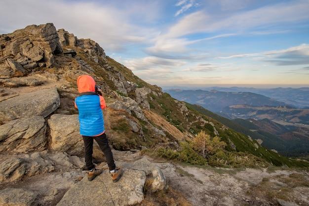 Путешественник мальчика маленького ребенка фотографируя в горах, наслаждаясь видом удивительного горного пейзажа.