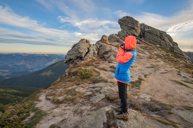 Young child boy hiker taking pictures in mountains enjoying view of amazing mountain landscape.