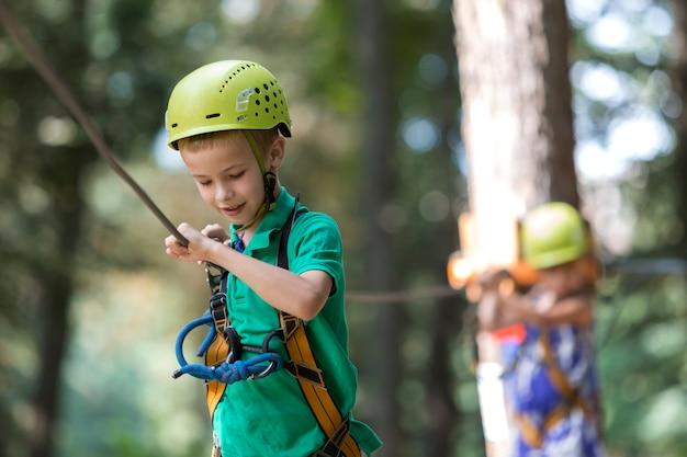 Мальчик маленького ребенка в ремнях безопасности и шлем прикрепленный с штуцером к кабелю на пути веревочки в парке.