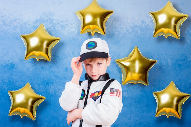 Young child boy male playing in astronaut in white astronaut costume and dreaming about flying into cosmos through the stars staying near gold star's balloons