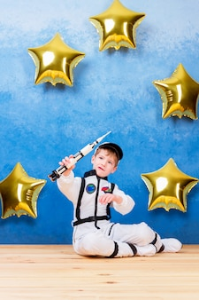 Young child boy male playing in astronaut with rocket in white astronaut costume and dreaming about flying into cosmos through the stars staying near gold star's balloons